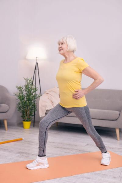 Blijf actief thuis - oudere vrouw doet oefeningen in huiskamer