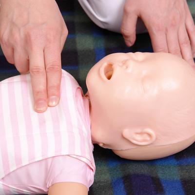 EHBO-cursussen - Detail van een babypop waar iemand tijdens de cursus EHBO bij baby's en kinderen reanimatie op oefent.